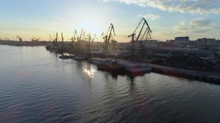 moorage : port infrastructure, commercial berth with lifting cranes for loading and unloading of ships of international trade on Sea coast against blue sky in Sunset and shiny water, aerial survey