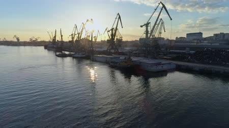 moorage : River port panorama with lifting cranes for loading and unloading of vessel of international trade on waterfront against blue sky in beautiful sundown and shiny water, drone view