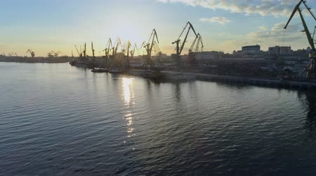 moorage : sea industry, commercial berth with lifting cranes for loading and unloading of ships of international trade on Sea coast against blue sky in sundown and shiny water, aerial view