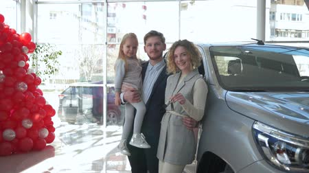 mama : happy family client in car dealership, portrait of smiling parents with little child girl on hands shows keys to new automobile purchased at auto shop
