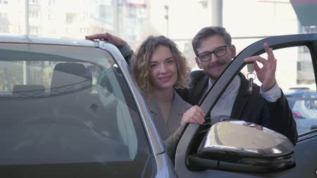 car dealership : portrait of happy car purchaser, young couple lovers delight new vehicle and showing keys in auto salon close-up