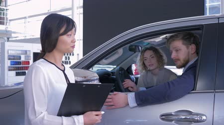 продавщица : portrait of saleswoman with family couple client which shows keys inside auto while purchase new car at sales center Стоковые видеозаписи