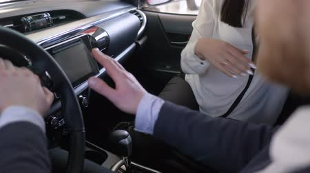 vendedora : saleswoman advises client after gives keys to car buyer and shakes hands sitting inside cabin close-up at dealership Stock Footage
