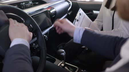 продавщица : successful car sale, female auto dealer advises client after hands over keys to customer and shakes hands sitting inside cabin close-up at showroom
