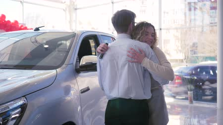 generoso : young spouse gives gift to beautiful wife which happy embrace and shows keys at car sales center