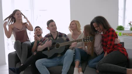 многонациональная : friends running and jump on the sofa and dance to the guitar, boys and girls have fun at the home party Стоковые видеозаписи