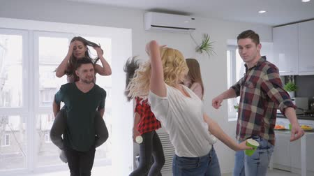 plastic cups : multiracial group of friends fun dancing with plastic cups in their hands in a large modern apartment at a home party