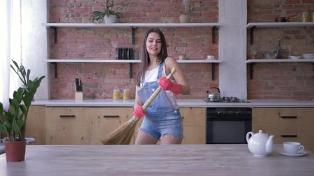 housekeeper : household chores, cheerful housewife girl fooling around and dancing in broomstick during House cleaning on cuisine