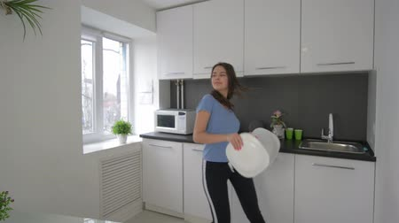 ama de llaves : alone at home, funny housewife fooling around and sings with dishes in hands at cuisine in weekend, slow motion