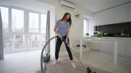 housekeeper : General cleaning, cheerful housewife female doing cleaning vacuums and have fun dancing and sings in bright room at home Stock Footage