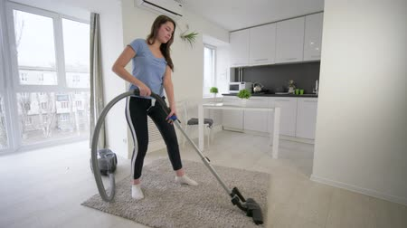 housekeeper : household duties, funny housekeeper girl doing cleaning vacuums and have fun dancing and sings in bright room at home Stock Footage