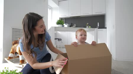 ищу : children entertainment, little cute baby in cardboard box playing hide-and-seek with mom and claps hand in bright room