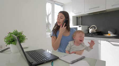 стресс : combining work and parenting, mother with crying little son while working on laptop computer and talking on mobile phone sitting at table in kitchen at home Стоковые видеозаписи