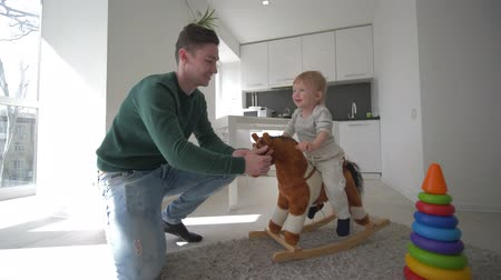 peluş : games with children, happy father playing with cute son on plush horse seating and swinging at home in bright kitchen