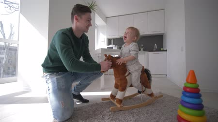 peluş : happy childhood, young dad playing with nice infant boy on plush equine seating and swinging at home in bright kitchen