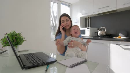 crying baby : multitasking mother with crying baby boy while working on laptop computer and talking on smartphone sitting at table in kitchen at home