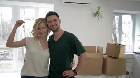 relocate : relocation to new home, portrait of smiling Lovers guy with girl show keys to apartment and hug while housewarming on background of cardboard boxes Stock Footage