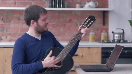 com cordas : funny instrumentalist male learning play guitar uses laptop computer with online video training and relish music at home Stock Footage