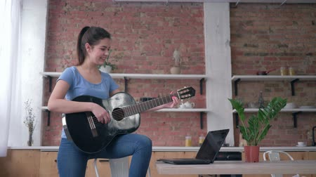 gitáros : musical hobby, smiling instrumentalist girl learning play stringed musical instrument uses laptop computer with online video training and enjoy music at home Stock mozgókép