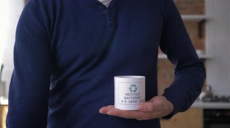 smaltimento : collecting used batteries, man puts old batteries into container with three chasing arrows of the international recycling logo then show thumb up gesture