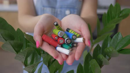 alkaline : environment and ecology, female hands holding alkaline batteries heap over green natural background