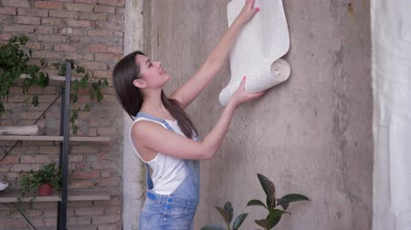 decorating apartment and people, beautiful girl choose wallpaper of the samples near empty wall during renovation in room