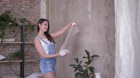 housework, pretty brunette house owner unrolling new wallpaper on wall during repairs at home