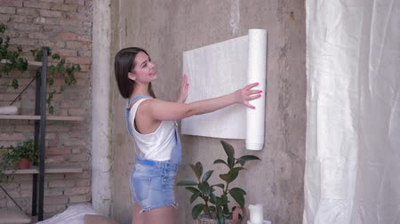riparazioni : interior design, portrait of young woman house owner unrolling new wallpaper near wall during repairs at apartment
