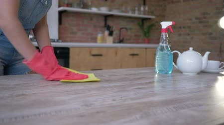 biscate : female hands in gloves with rag easily cleaning table from dust and stains with new detergent at kitchen Stock Footage