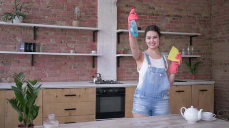 trapo : housewife in denim overalls and gloves with rag and cleaning spray in hands posing for the camera at kitchen