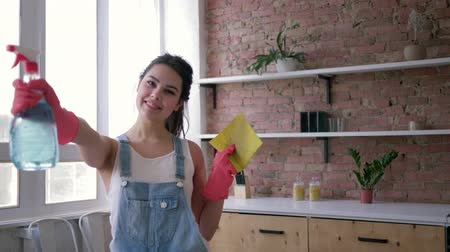домохозяйка : portrait of happy housewife in denim overalls and gloves holds cleanser spray and duster in hands during the cleaning of the kitchen at apartment Стоковые видеозаписи