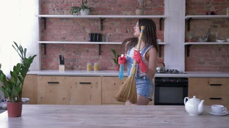 süpürge : spring cleaning, smiling girl in denim overalls and gloves happily has fun in the kitchen with a broom and cleanser spray in her hands Stok Video