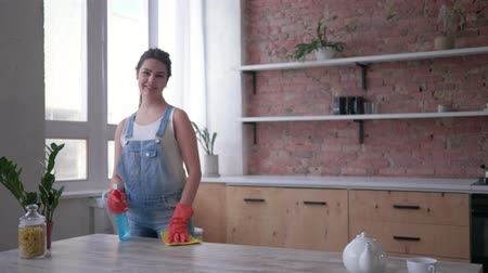 dÉsinfecter : spring general cleaning, young woman in gloves cleaning table with rag and cleanser spray then looks on camera and smiles at kitchen