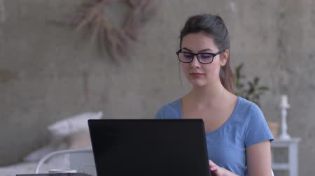correspondência : business girl with glasses working at home sitting at a laptop typing text and looking at the screen close-up Stock Footage
