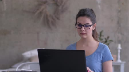 correspondência : e-learning, modern girl in eyeglasses looks into the laptop screen and types text on the keyboard at home close-up