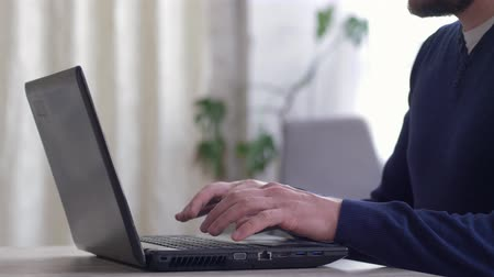 men hands open the laptop and type text on the keyboard then closes the computer on workplace
