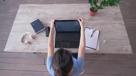 netbook : top view of freelancer girl clothes glasses and headphones then typing text on laptop keyboard sitting at the table during working