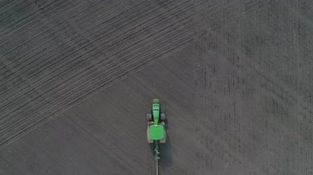 akkerland : drone view of a modern green tractor with plows works the land in the field at spring Stockvideo
