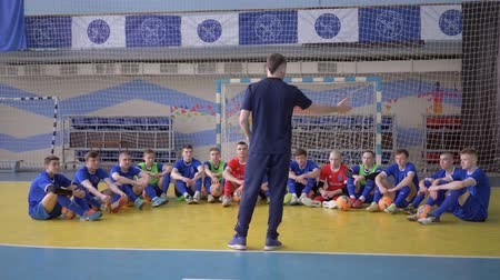 contestant : KHERSON, UKRAINE - APRIL 02, 2019: football team of young guys listen to coach instructions tactic before match at sports hall