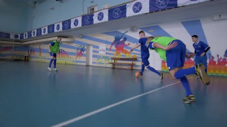 konkurenti : KHERSON, UKRAINE - APRIL 02, 2019: soccer training, sport Team of teenagers football players pass ball to score goal at sports hall