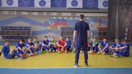 contestant : KHERSON, UKRAINE - APRIL 02, 2019: team spirit, trainer gives instructions for teenagers football players before match at sports hall