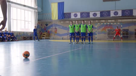 вратарь : KHERSON, UKRAINE - APRIL 02, 2019: football competitions in sports hall, sportsman kicks ball to score penalty goal in gate with goalie Стоковые видеозаписи