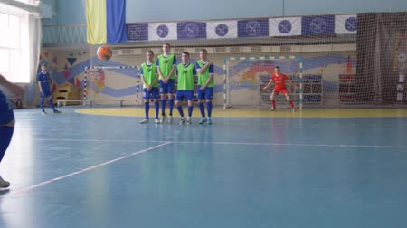 contestant : KHERSON, UKRAINE - APRIL 02, 2019: football game, soccer player male kicks ball to score penalty goal in gate with goalkeeper at sports hall