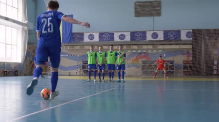 вратарь : KHERSON, UKRAINE - APRIL 02, 2019: sport game, football player guy kicks ball to score penalty touchdown in gate with goalie indoors Стоковые видеозаписи