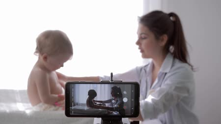 relieves : blogging, popular vlogger female doctor filming new episode for vlog on smartphone during medical examination of baby for followers, unfocused