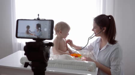 relieves : online lecture, famous blogger family doctor with baby examining little patient using stethoscope and leads live learning broadcast on mobile phone for followers