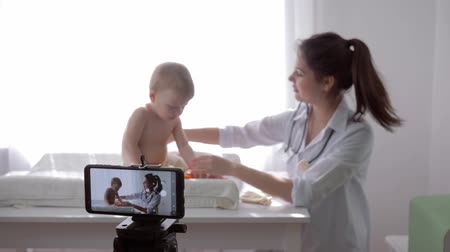 relieves : online training, famous vlogger girl doctor recording social media video on cell phone during medical examination of toddler in streaming live, unfocused Stock Footage