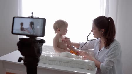 relieves : video lesson, famous blogger mother medic examining son using stethoscope and leads live learning broadcast on smartphone for followers in social networks