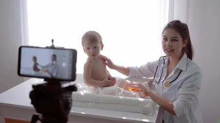 relieves : video teaching, famous blogger woman family doctor teaches subscribers to examine child at home and recording social media video on smartphone in streaming live