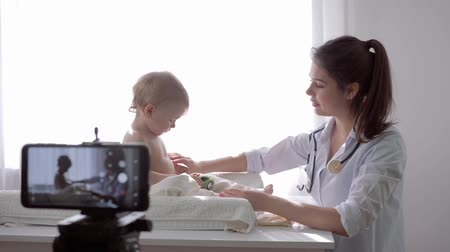 relieves : videoblog, popular blogger woman medic recording live tutorial video on mobile phone during medical examination of child for followers